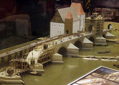 Model zachycuje také některé dobové lešenářské konstrukce, mechanizační stroje, dopravu materiálů, řemeslnické zázemí i běžný život kolem staroměstského břehu.