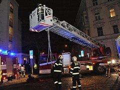 K záchraně ženy hasiči použili žebřík.