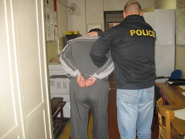 Zadržený muž je eskortován do vazební věznice.