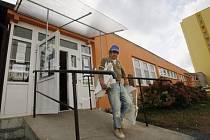 Dělník vynáší sádrokartonové kusy ze stropního podhledu, k jehož zřícení došlo v úterý 30. září 2008 v mateřské škole v Hurbanově ulici v pražské Krči.