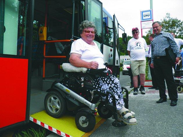 Seniorka vystupuje ze speciálního autobusu.
