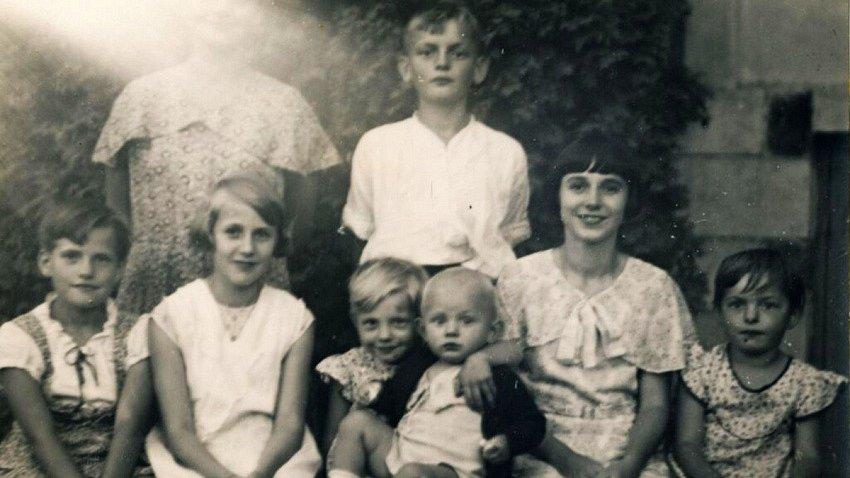 Věra (uprostřed s mladším bratrem Zdeňkem na klíně) se svými sourozenci a maminkou (na fotografii není k rozeznání).