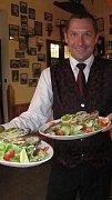 """""""Úřadující"""" vedoucí restaurace U Koně v Klokočné Jan Kadlec servíruje říčního pstruha na jarním salátu, kterého připravil šéfkuchař David Špidra."""