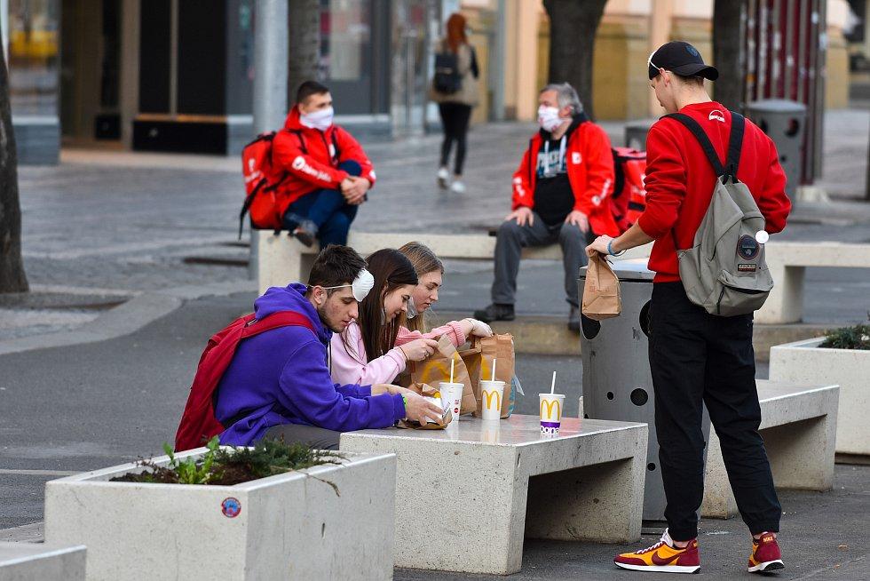 Prázdné ulice Prahy a lidé s rouškami 18. března 2020. Skupinka mladých u MC Donalds.