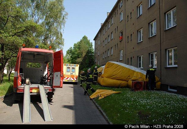 Pod okny hasiči pohotově rozprostřeli tlumící plachtu, nakonec zůstala naštěstí nevyužita.