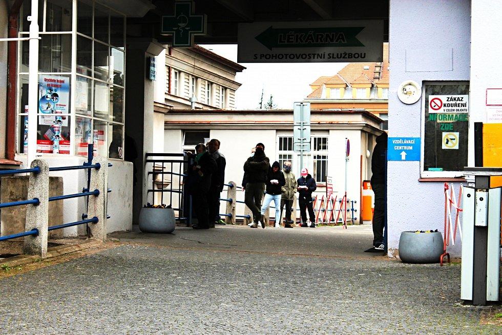 Lidé čekají v Nemocnici Na Bulovce ve frontě na odběr vzorků kvůli novému koronaviru.