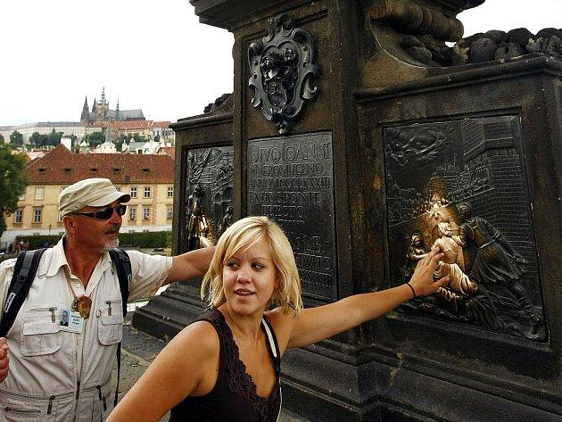 SVĚTEC NEBO PES. Který je ten pravý? Stovky lidí denně hladí reliéf u sochy sv. Jana Nepomuckého s nadějí, že se jim splní tajné přání.