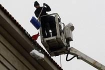 Dělníci odstraňují z vysokozdvižné plošiny sníh ze střechy Městské knihovny ve Valentinské ulici v centru Prahy. Padající těžký mokrý sníh ohrožuje v těchto dnech zejména chodce.
