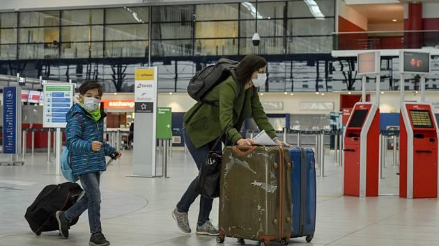 Žena s dítětem v rouškách na letišti v Ruzyni.