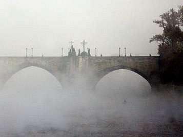 Tajemný Karlův most v ranní mlze.