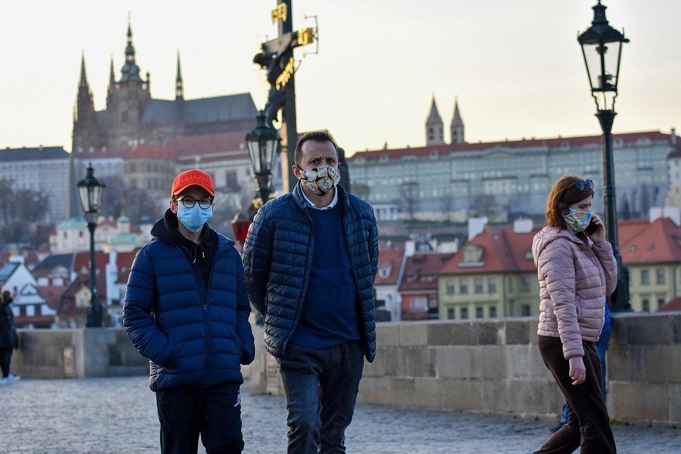 Prázdné ulice Prahy a lidé s rouškami 18. března 2020. Karlův most v době karantény, pohled na Pražský hrad.