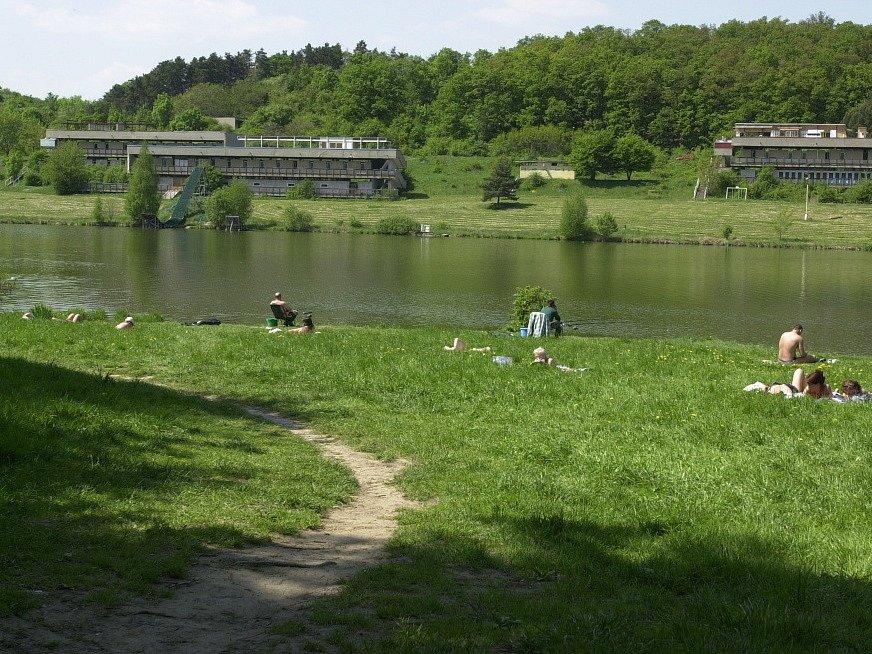 KOUPALIŠTĚ DŽBÁN leží v těsném sousedství přírodní rezervace Divoká Šárka. Na březích Džbánu by majitel pozemků rád postavil nové obytné domy. Na místě zchátralého zázemí koupaliště (v pozadí). Praha 6 to odmítá.