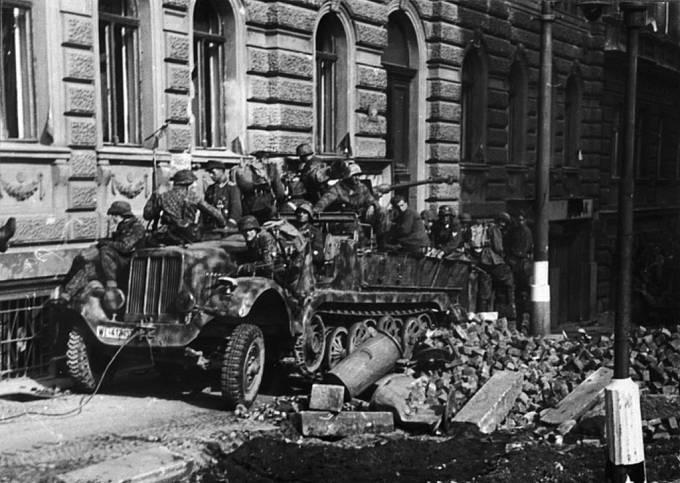 Ustupující jednotky Wehrmachtu před kavárnou Demínka na Vinohradech v Praze, během Květnového povstání.