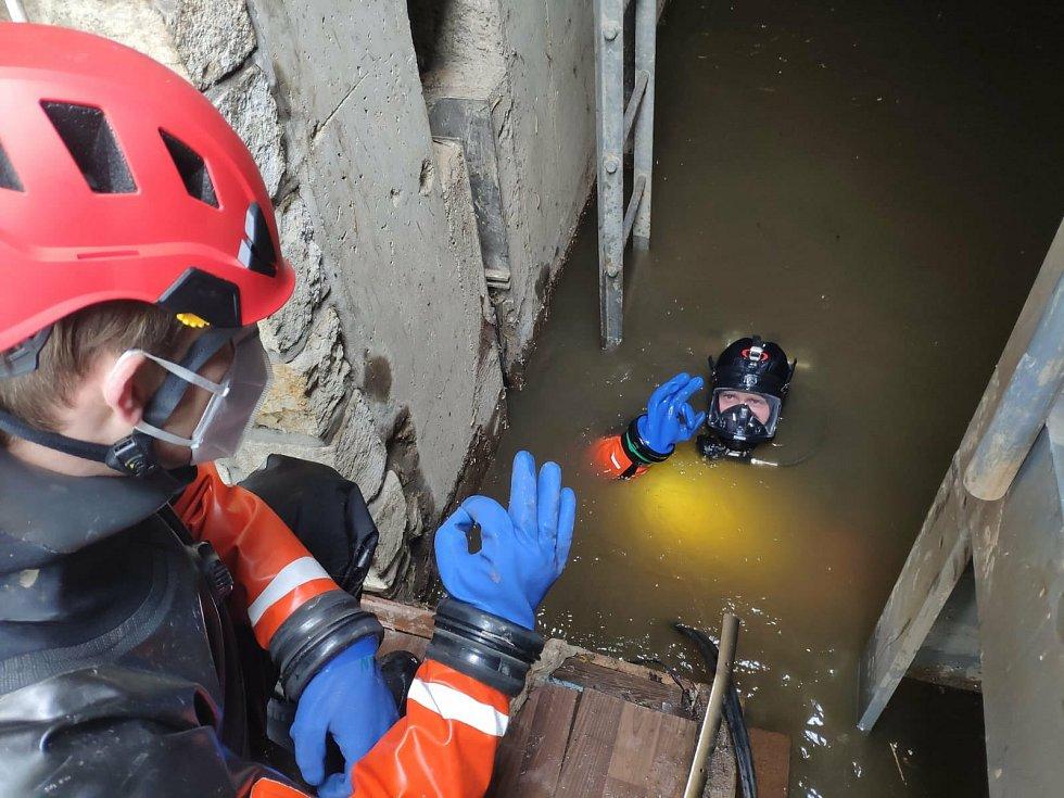 Potápěči z vody kontrolují stav uzavřených protipovodňových vrat na Čertovce.