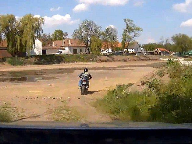 Motorkář sjel z hlavní silnice a vjel do vypuštěného Kovářského rybníka. Pak pokračoval po polní cestě, až dojel do výběhu pro koně.