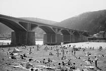 Pražané chytají v létě 1962 sluneční paprsky u Branického železničního mostu (lidově přezdívaného most Inteligence). Sedící pár v popředí fotky jsou rodiče editora Pražského deníku. Poznáte i vy někoho na fotce?