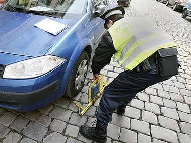 POSTRACH ŘIDIČŮ. Strážník nasazuje botičky autům zaparkovanýmmimo povolená místa.