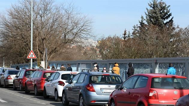 Lidé čekají na test na nákazu novým koronavirem u plotu Thomayerovy nemocnice.