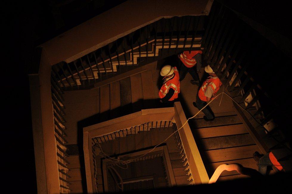 Schodiště je osvětlováno průmyslovými lampami.