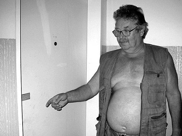 TADY SE VRAŽDILO. Předseda domovní samosprávy Miloš Hlaváčekukazuje na stále zapečetěné dveře bytu, za kterými došlo ke krvavétragédii, která otřásla všemi nájemníky domu.