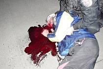 Muž ležící na chodníku v tratolišti krve v Soběslavské ulici v Praze.