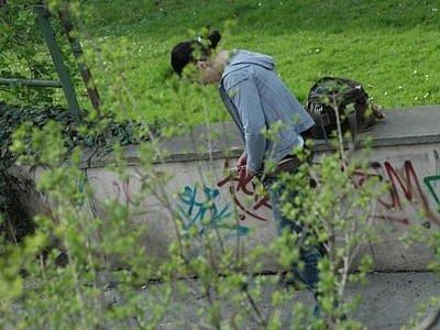 Mladá žena si v centru Prahy píchá drogu.