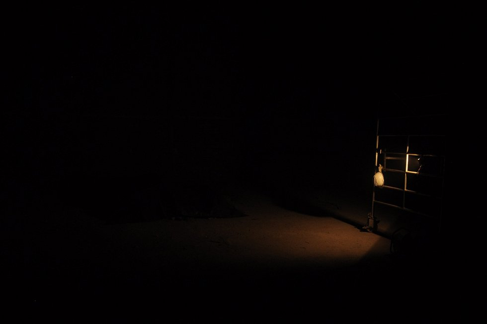 Zkušebnu osvětluje pouze malé světlo.