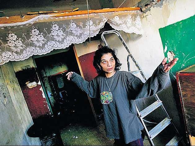 Obyvatelka poukazuje na katastrofální stav domu.