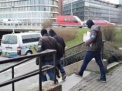 Eskorta muže podezřelého z loupežného přepadení patnáctiletého mladíka v Modřanech.
