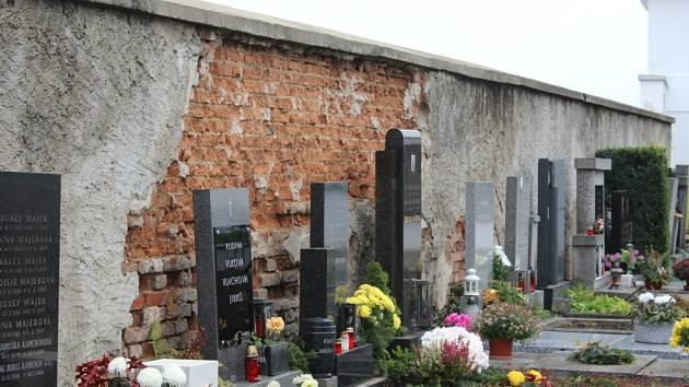 Naklánějící se obvodová zeď na hřbitově Jinonice, u které hrozí pád do hřbitova a sesun přidružené vozovky.
