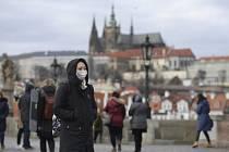 Turistka s rouškou prochází 29. ledna 2020 po Karlově mostě v Praze. Zájem o ochranné pomůcky se v posledních dnech zvýšil kvůli hrozbě nového koronaviru šířícího se z Číny. Nákaza se zatím v Česku u žádného z případů podezření na infekci nepotvrdila.