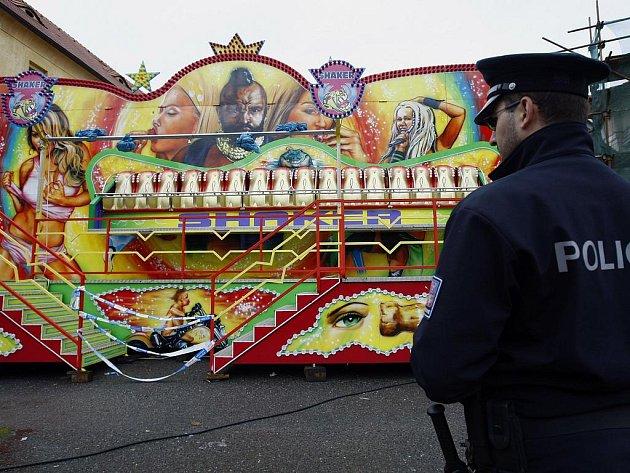 MÍSTO NEŠTĚSTÍ. Policista hlídá pouťovou atrakci. Visutá točící lavice se nečekaně otevřela a lidé vypadli ven. Příčinu vyšetřuje policie.