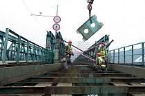 Kousek po kousku začíná mizet příhradový most přes Vltavu, který dlouhá léta sloužil jako dočasná přepravní komunikace z Holešovic do Kobylis. Vše už je minulostí, využití demontované konstrukce je zatím takříkajíc ve hvězdách.