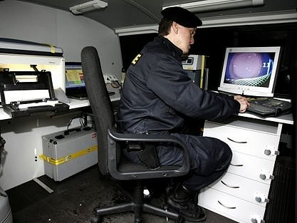 UKÁZKA. Policista předvádí, jak funguje technické vybavení vozu.