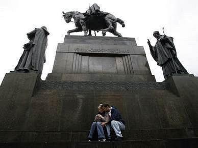 Po odstranění řetězu okolo sochy lidé na podstavci relaxují.