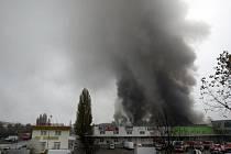 PO OSMNÁCTI HODINÁCH. Z haly se valí hustý dým, hasiči stále bojují s ohněm.