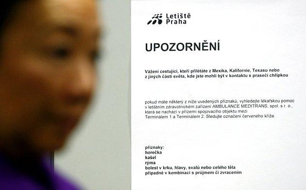 Cedule varující před nákazou prasečí chřipkou a popisující průběh onemocnění informují cestující na ruzyňském letišti. Snímek je z 28. dubna 2009.