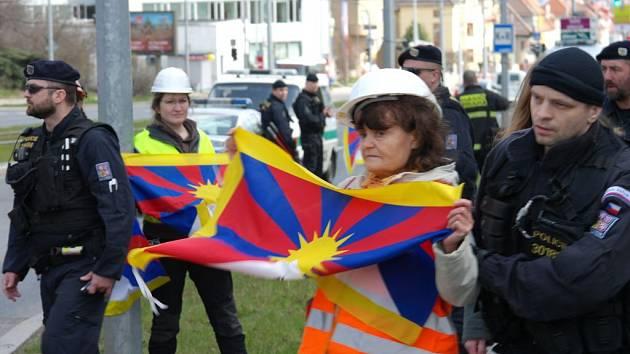 Lidé protestující proti vstřícnosti české strany vůči čínskému prezidentovi i proti jeho samotnému příletu vyměňovali čínské prapory za symboly Tibetu v ulicích Arabská a Horoměřická