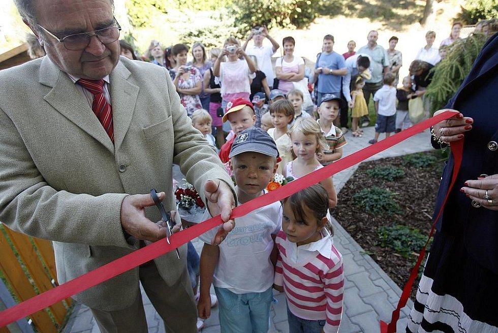 Na snímku střihá slavnostní pásku starosta obce Stanislav Kettner.
