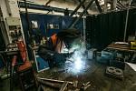 Pracoviště svařování ve výrobní hale, na fotografii pracovník svařuje víka skříňky odvodnění výměny.