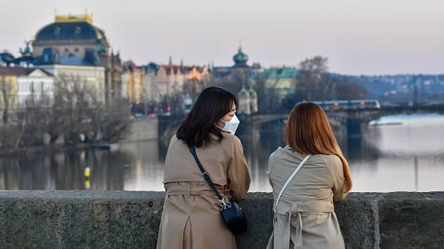 Prázdné ulice Prahy a lidé s rouškami 18. března 2020. Osamělé turistky na Karlově mostě.