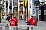 Prázdné ulice Prahy a lidé s rouškami 18. března 2020. Kurýři na rozvoz jídla čekají na objednávku.