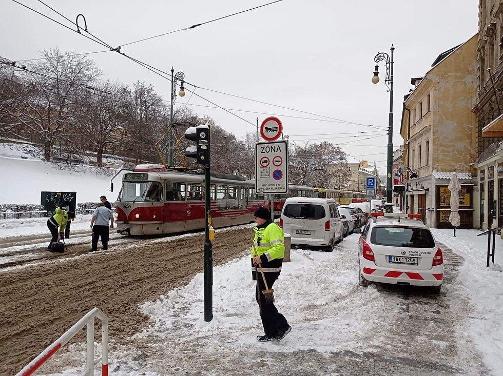 """Sněhová kalamita způsobila 8. února 2021 problémy v městské hromadné dopravě. Snímek zachycuje """"přesvědčování"""" výhybky na Újezdě."""