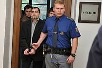 Před Krajským soudem v Praze se zpovídá pětice mužů z činu, který obžaloba vidí jako pokus o vraždu seniorky. Jako hlavní pachatelé jsou souzeni Vladimír Novotný (s brýlemi a vousy) a František Kopena (v hnědé bundě).