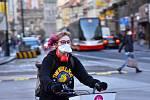 Prázdné ulice Prahy a lidé s rouškami 18. března 2020. Slečna na kole s rouškou.