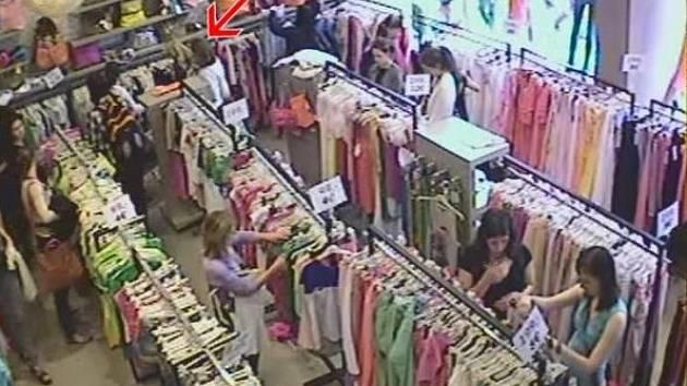 Kapsářky se snaží odcizit peněženku telefonující kriminalistce (u zdi s kabelkami).