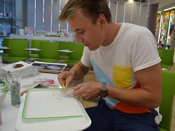 Designér František Fiala usvého oceněného prkénka, vruce má zdobící krabičku spinzetou na zdobení dortů sladkými posypy a kuličkami.
