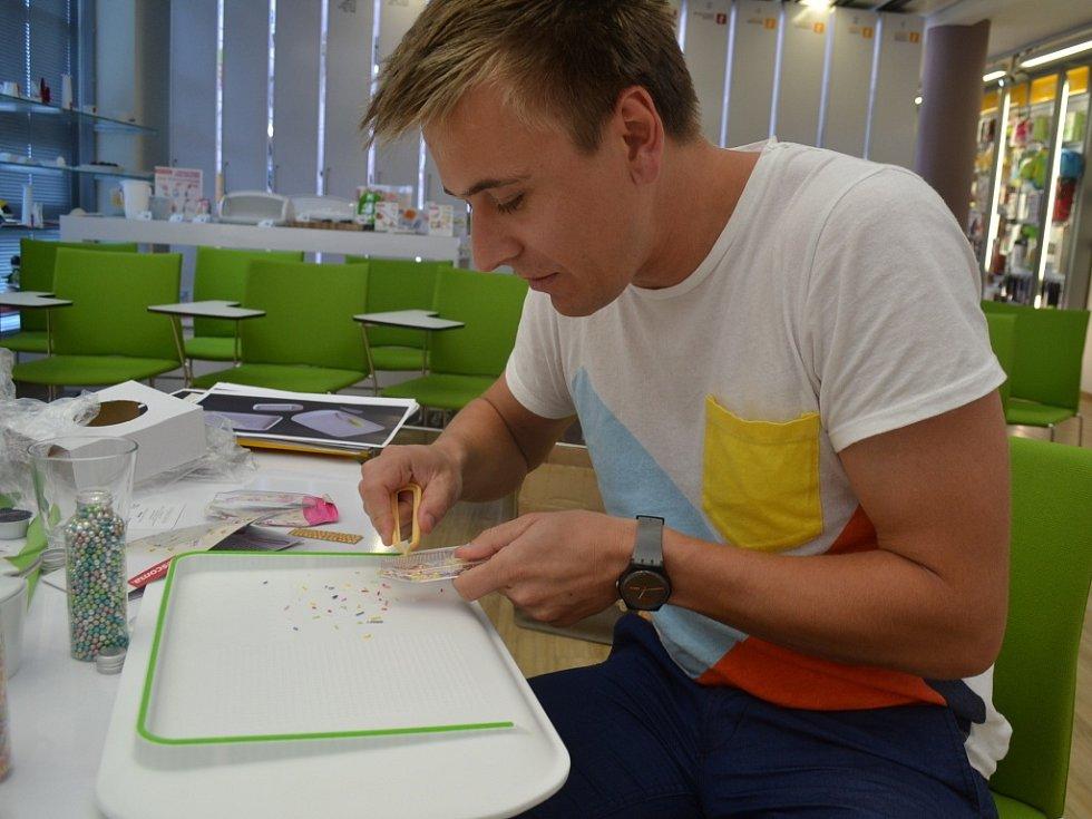 Designér František Fiala u svého oceněného prkénka, v ruce má zdobící krabičku s pinzetou na zdobení dortů sladkými posypy a kuličkami.