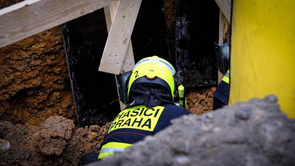 Pražští hasiči se snaží vyprostit dělníka, jehož na Smcíhově zavalila zemina. Zásah probíhá v těžkých podmínkách.