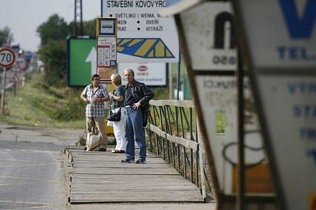 Autobusová zastávka Fruta. Nástupiště tvoří jakési dřevěné pódium. To už ale zjevně dosloužilo. Popraskaná prkna hrozí zraněním nejen starým lidem.